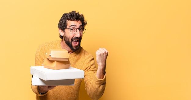 Junger verrückter bärtiger mann, der fastfood mit einem kopienraum wegnehmen