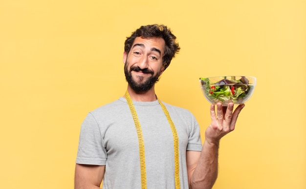 Junger verrückter bärtiger mann, der glücklichen ausdruck nährt und einen salat hält