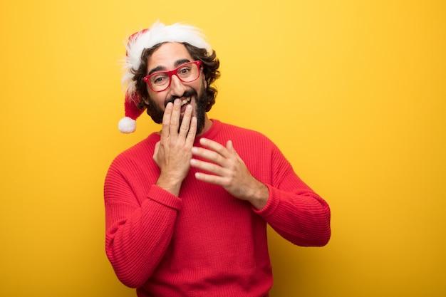 Junger verrückter bärtiger mann, der rote gläser und weihnachtsmann-hut trägt