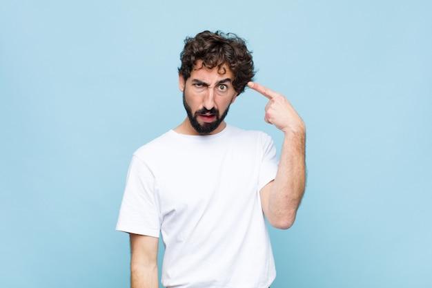 Junger verrückter bärtiger mann, der sich verwirrt und verwirrt fühlt und zeigt, dass sie verrückt, verrückt oder verrückt gegen flache wand sind
