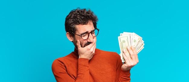 Junger verrückter bärtiger mann. dollar-banknoten-konzept