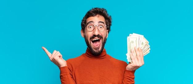 Junger verrückter bärtiger mann. einen triumph feiern wie ein sieger. dollar-banknoten-konzept