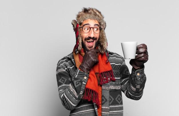 Junger verrückter bärtiger mann. glücklicher und überraschter ausdruck. denkender oder zweifelnder ausdruck und tragen winterkleidung
