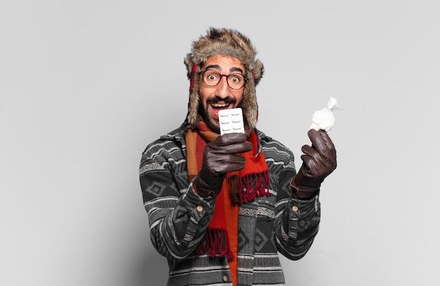 Junger verrückter bärtiger mann. glücklicher und überraschter ausdruck und das tragen von winterkleidung. krankheitskonzept