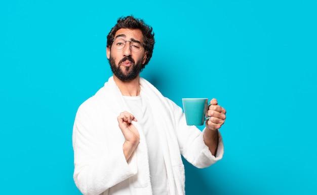 Junger verrückter bärtiger mann mit bademantel mit kaffeetasse
