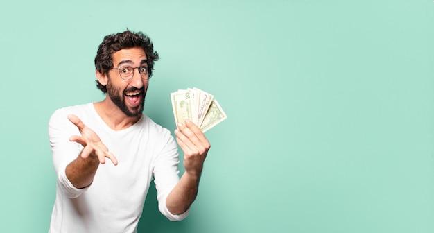 Junger verrückter bärtiger mann mit dollar-banknoten