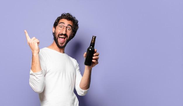 Junger verrückter bärtiger mann mit einem bier
