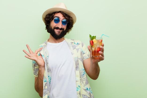 Junger verrückter bärtiger mann mit einem cocktail. touristisches konzept