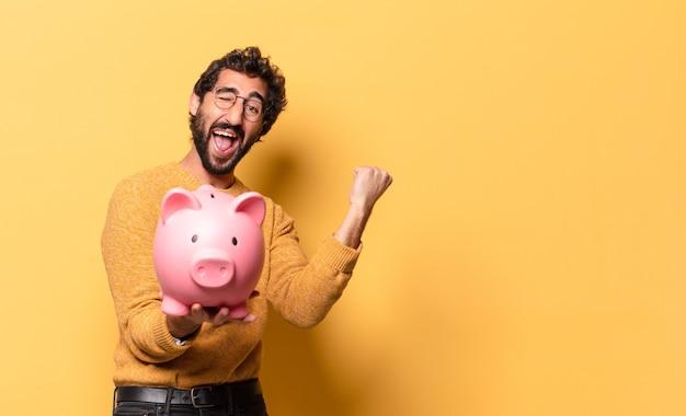 Junger verrückter bärtiger mann mit einem sparschwein