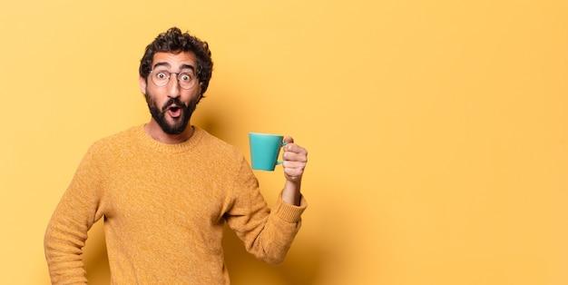 Junger verrückter bärtiger mann mit einer kaffeetasse