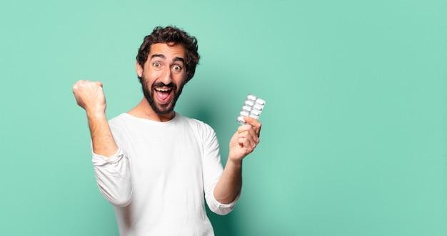 Junger verrückter bärtiger mann mit einer pillentablette
