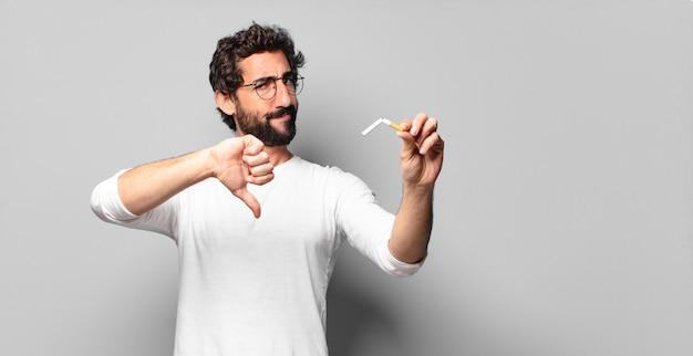 Junger verrückter bärtiger mann mit einer zigarette. nichtraucherkonzept.