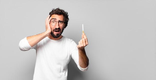 Junger verrückter bärtiger mann mit einer zigarette. rauchverbot.