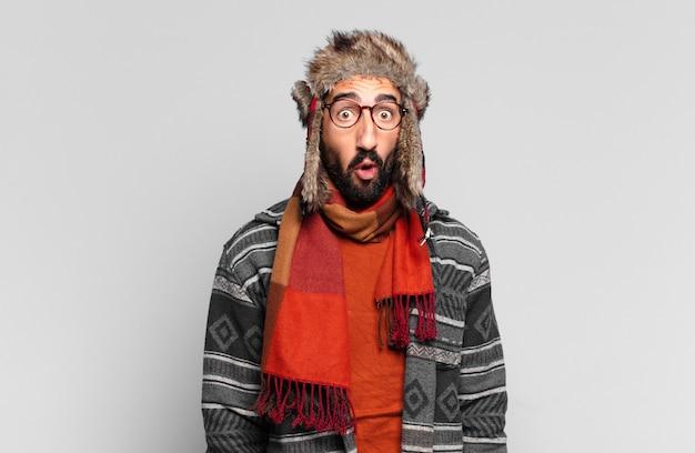 Junger verrückter bärtiger mann. schockierter oder überraschter ausdruck und das tragen von winterkleidung winter