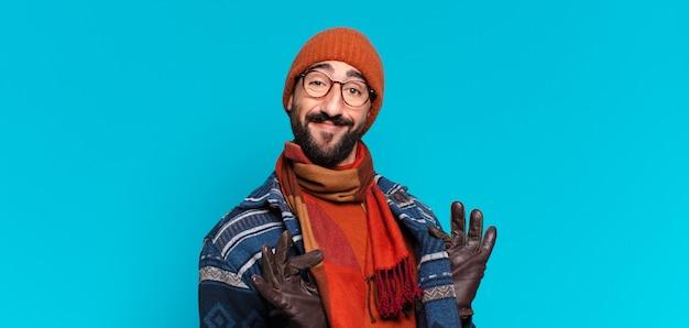 Junger verrückter bärtiger mann stolzer ausdruck und trägt winterkleidung winter