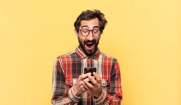 Junger verrückter bärtiger mann überraschter ausdruck und hält ein telefon
