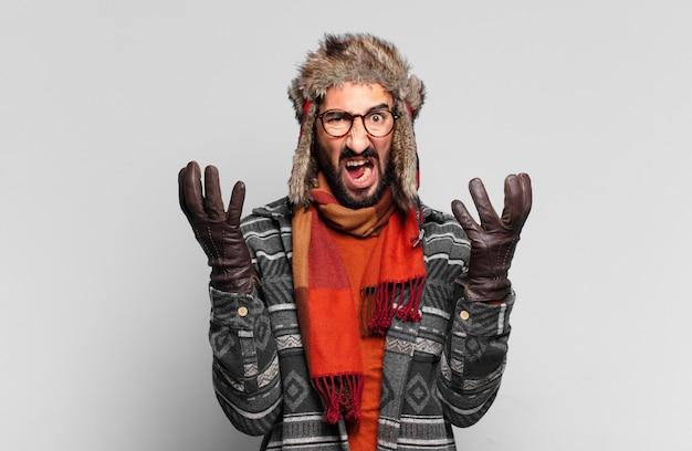 Junger verrückter bärtiger mann und trägt winterkleidung