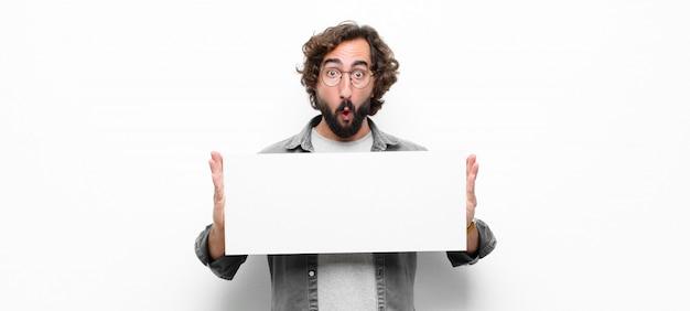 Junger verrückter cooler mann, der ein plakat gegen weiße wand hält