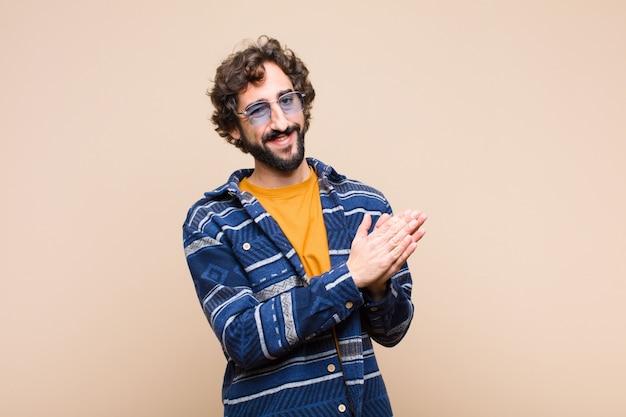 Junger verrückter cooler mann, der glücklich und erfolgreich fühlt, lächelt und hände klatscht und glückwünsche mit einem applaus sagt