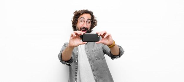 Junger verrückter cooler mann, der sein smartphone gegen weiße wand benutzt