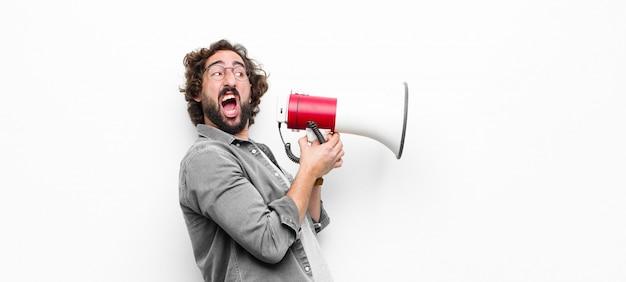 Junger verrückter cooler mann mit einem megaphon gegen weiße wand