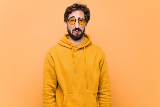 Junger verrückter cooler trauriger ausdruck gegen orange wand