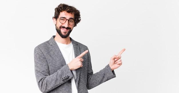 Junger verrückter geschäftsmann, der glücklich lächelt und zur seite und nach oben zeigt, wobei beide hände objekt im kopierraum gegen flache wand zeigen