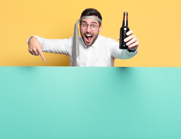 Junger verrückter geschäftsmann mit einer bierflasche, die gute nachrichten feiert