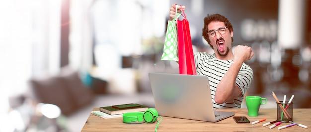 Junger verrückter grafikdesigner auf einem schreibtisch mit einem laptop Premium Fotos