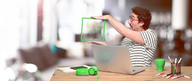 Junger verrückter grafikdesigner auf einem schreibtisch mit einem laptop