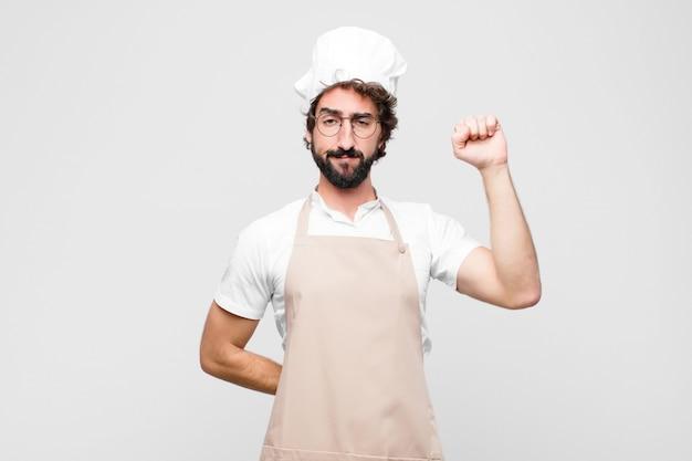 Junger verrückter koch, der sich ernst, stark und rebellisch fühlt, die faust erhebt, protestiert oder für die revolution gegen die weiße wand kämpft