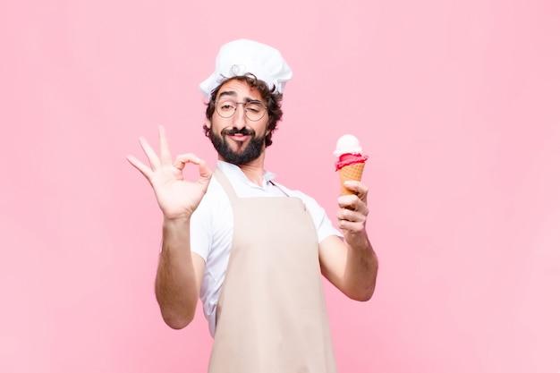 Junger verrückter kochmann mit einem eis gegen rosa wand