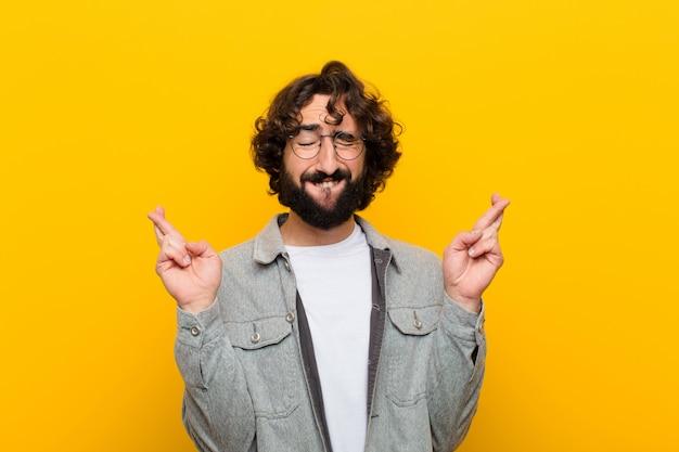Junger verrückter mann, der besorgt beide finger kreuzt und lächelt, sich besorgt fühlt und gutes glück gegen gelbe wand wünscht oder hofft