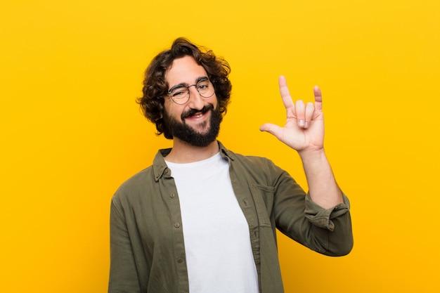 Junger verrückter mann, der der überzeugten positiven und rebellischen herstellung des glücklichen spaßes felsen oder schwermetallschild mit der hand glaubt
