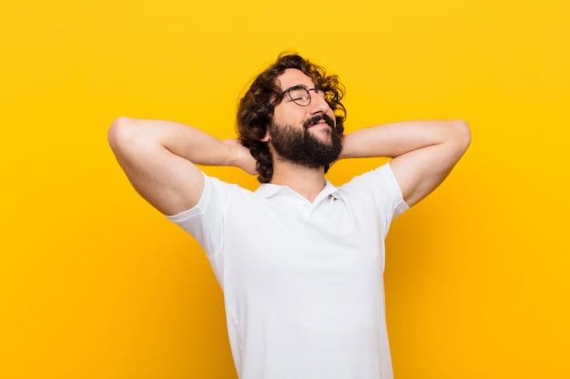 Junger verrückter mann, der entspannt, zufrieden und sorglos lächelt und sich fühlt, positiv lacht und gelbe wand kühlt