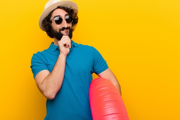 Junger verrückter mann, der mit einem glücklichen überzeugten ausdruck mit der hand auf dem kinn sich wundert und zur seite gegen orange wand schaut lächelt