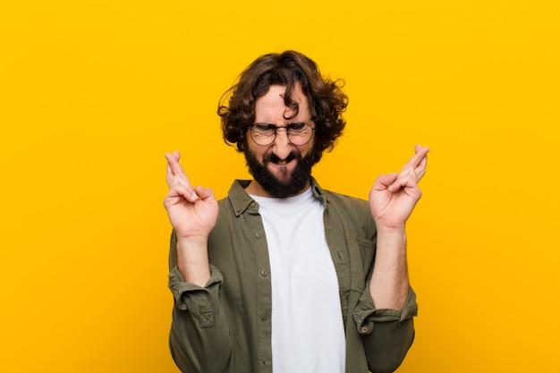 Junger verrückter mann, der nervös und hoffnungsvoll sich fühlt, finger kreuzt, für gelbe wand des guten glücks betet und hofft