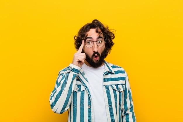 Junger verrückter mann, der überrascht, mit offenem mund, entsetzt, einen neuen gedanken verwirklichend, gelbe wand der idee schaut