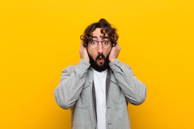 Junger verrückter mann, der unangenehm entsetzt, erschrocken oder besorgt, mund weit offen und beide ohren mit handgelbwand bedeckend schaut