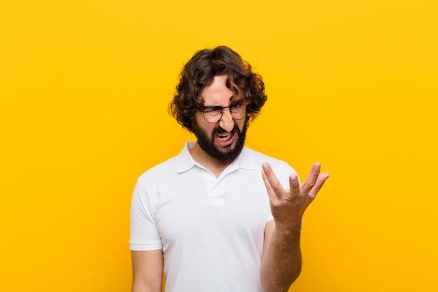 Junger verrückter mann, der wütend, genervt und frustriert aussieht und wtf schreit oder was mit dir an der gelben wand los ist