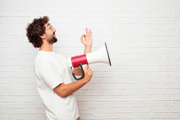 Junger verrückter mann mit einem megaphon gegen backsteinmauer.