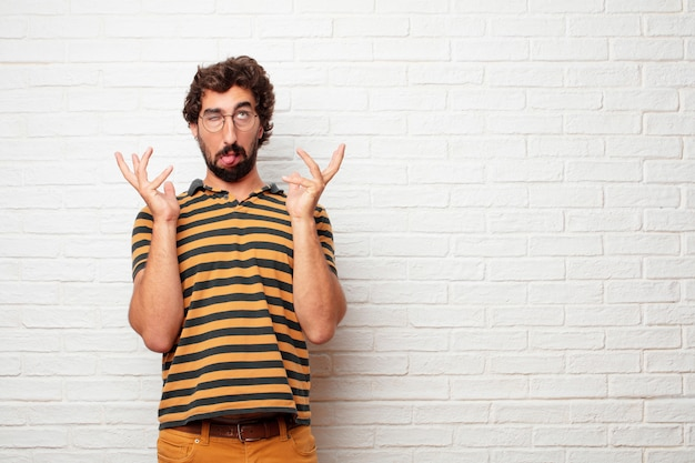 Junger verrückter oder dummer mann, der gefühle gegen backsteinmauerhintergrund gestikuliert und ausdrückt