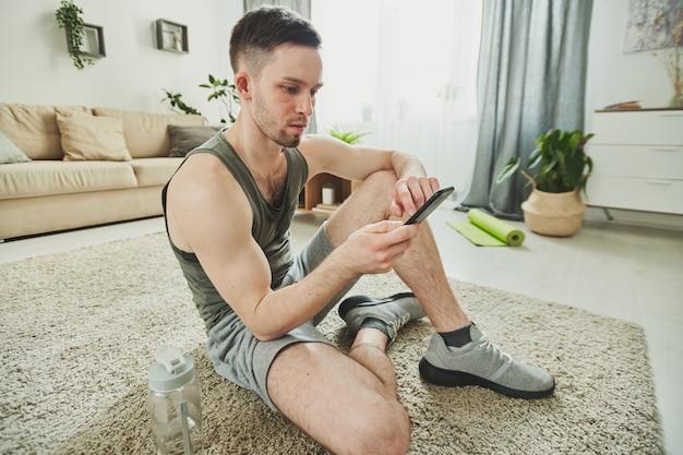 Junger verschwitzter athlet in der sportbekleidung, die auf teppich im wohnzimmer sitzt, während durch nachrichten im smartphone in der pause nach dem training gescrollt wird