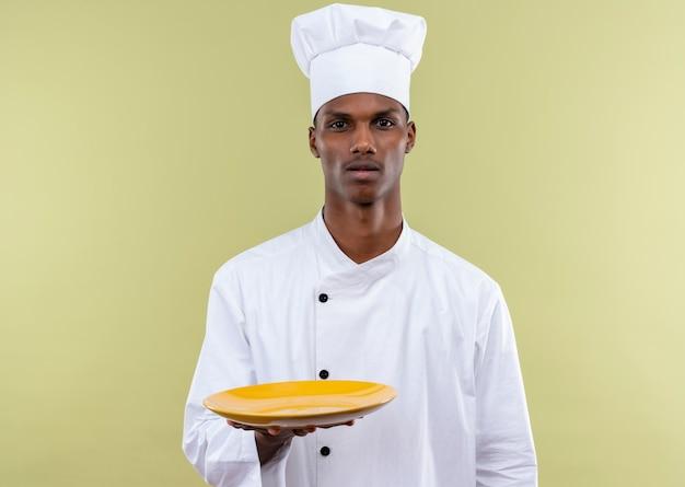 Junger verwirrter afroamerikanischer koch in der kochuniform hält platte lokalisiert auf grüner wand