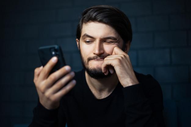 Junger verwirrter mann, der im smartphone auf dem hintergrund der schwarzen backsteinmauer schaut.