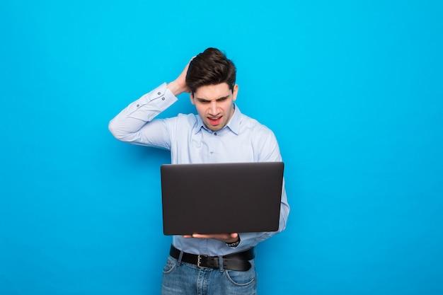 Junger verwirrter mann, der laptop lokalisiert auf blauem raum hält