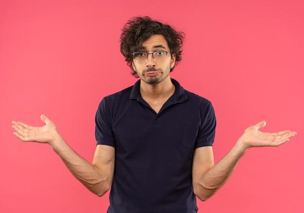 Junger verwirrter mann im schwarzen hemd mit optischer brille geldbörsen lippen und hält hände offen isoliert auf rosa wand