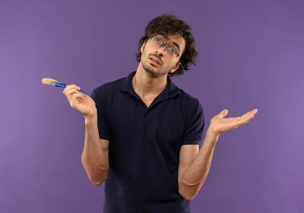 Junger verwirrter mann im schwarzen hemd mit optischer brille hält pinsel und schaut isoliert auf violetter wand auf