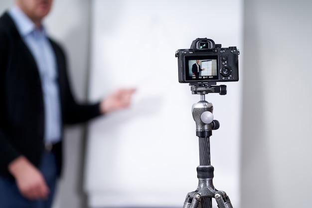 Junger videoblogger, der wichtige daten auf flipchart, online-bildungskonzept präsentiert