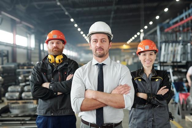 Junger vorarbeiter in abendgarderobe und helm und seine beiden selbstbewussten untergebenen in arbeitskleidung posieren